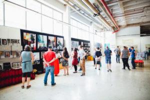 Besucher beschäftigen sich mit Kunst: supermART #9 im Jahr 2019 auf AEG in Nürnberg. Foto von Markus Spiske